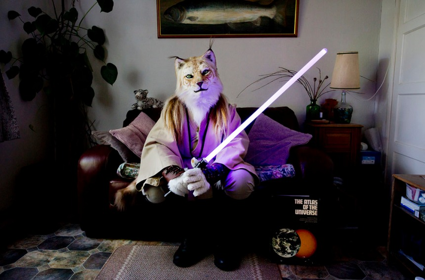 """Fangorn, a Jedi tiger sits in his living room, Swansea From the series"""" At Home With The Furries"""" Throughout the year furries dress up in costume or fur-suit inspired by anthropomorphic characters from cartoons, comic strips, myths and videogames. The people inside the suits are by day computer programmers, engineers, mortgage brokers, lecturers even fursuit makers. Most furries have an affinity with animals but some also like to role-play or fursuit for fun. Over the course of a few years, I gained the trust of the furries in the UK and some of their members allowed me to visit them at home, these photographs were taken all over the country. Contact tom@tombroadbent.com for licensing rights"""